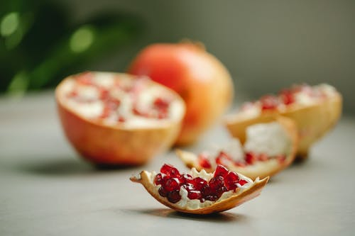 Chunk of ripe pomegranate with red seeds placed on surface near halves of tasty fruit on blurred background in kitchen