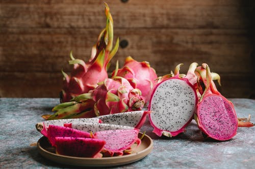 Ripe sliced dragon fruit with colorful flesh served on plate and placed on gray table against wooden wall in kitchen