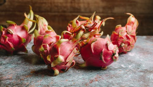 Heap of whole ripe tasty dragon fruits with pink peel placed on marble surface against wooden wall in light kitchen