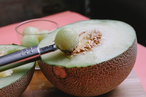Halved melon with scoop in kitchen