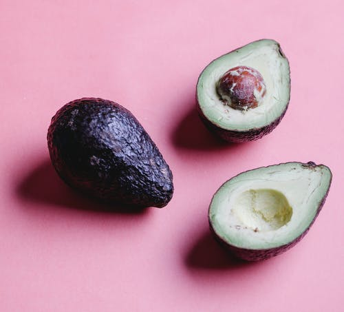 Composition of halved avocados on pink background