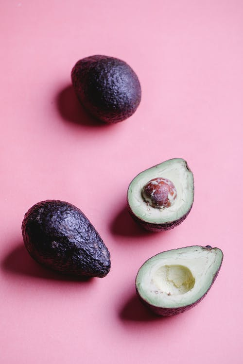 Ripe avocados on pink background