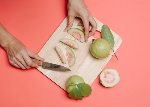 Crop person cutting guava on board