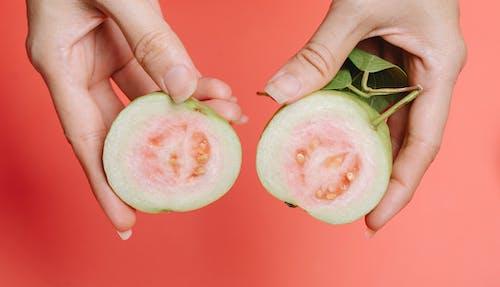 Crop woman showing halves of guava