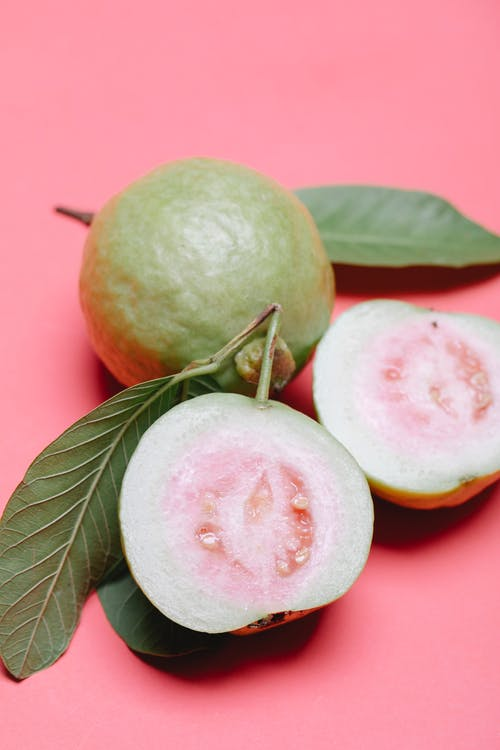 From above ripe fresh appetizing cut in half and whole fruits of guava on pink surface