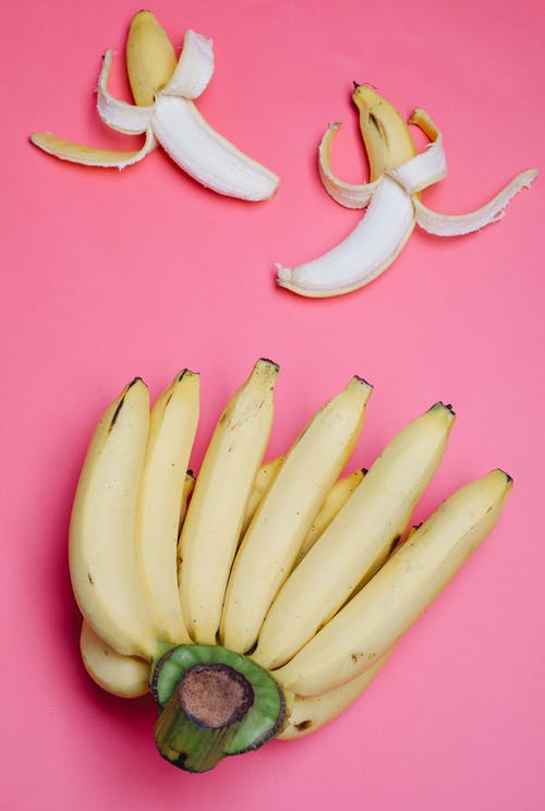 Peeled and unpeeled bananas on pink surface