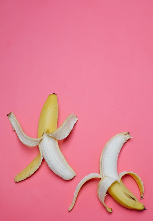 Peeled bananas on pink background