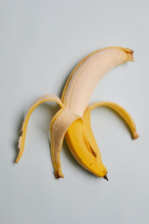 From above of half peeled ripe fresh tasty banana with yellow skin on white background