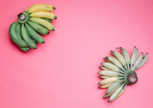 Hands of bananas on pink surface