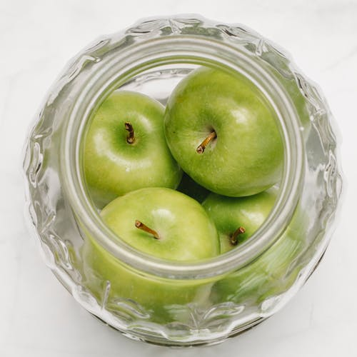 Green apples in glass bowl