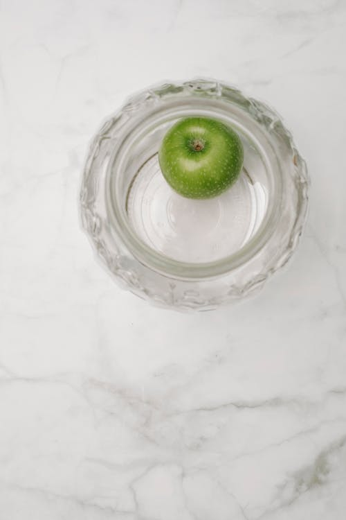 Top view of single fresh ripe tasty green apple in empty glass bowl on marble surface