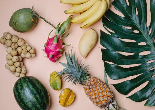 Tropical fruits and leaf on beige surface