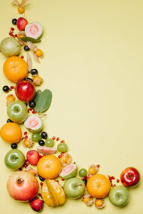 From above of different delicious ripe fresh juicy fruits and berries on beige background