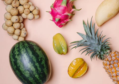 From above of mix of fresh colorful exotic fruits placed on pink background in light room