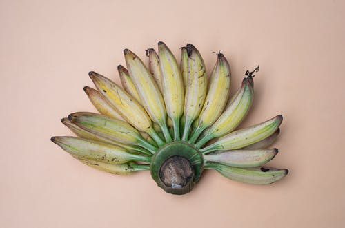 Top view composition of recently collected harvest of ripe fresh bananas placed on pink background