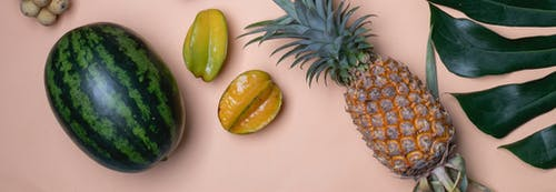Pineapple and carambolas placed near watermelon and palm leaf