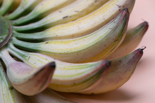 Bunch of fresh small bananas with dark spots located on pink surface