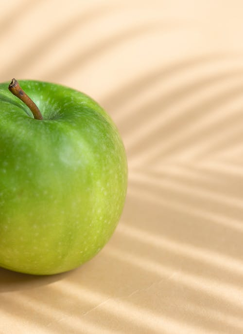 Fresh ripe green apple placed on white surface
