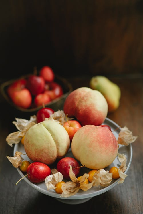 High angle of fresh ripe peaches with winter cherries and apples in bowl on table