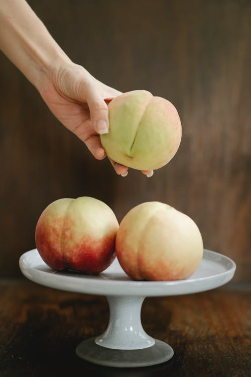 White stand with fresh peaches