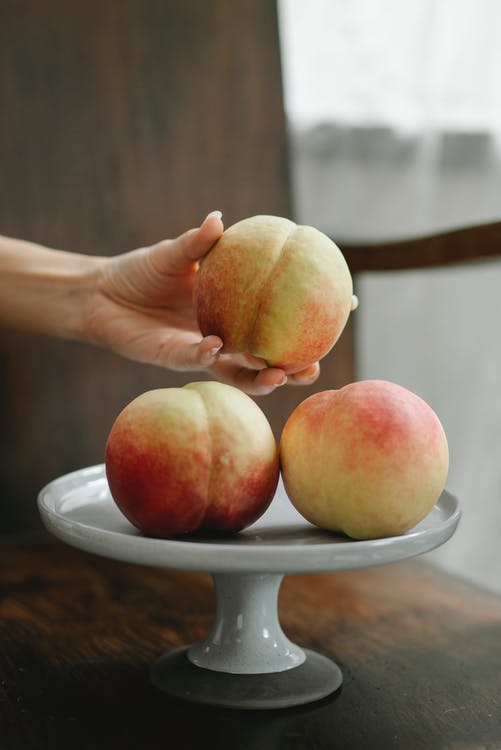 Unrecognizable woman taking fresh juicy ripe peach from white stand on table in kitchen
