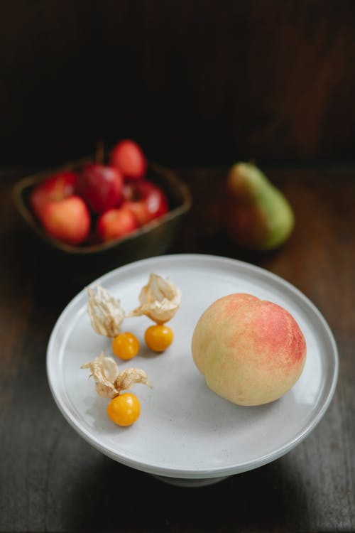 From above of fresh juicy peach and ripe amber cape gooseberries on white stand on table