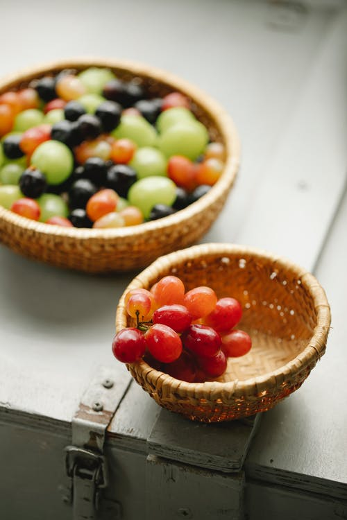 High angle of wicker bowls with fresh blueberries and green and red grapes
