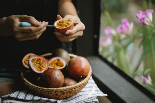 Unrecognizable woman picking up juicy pulp of passion fruit while cooking healthy lunch