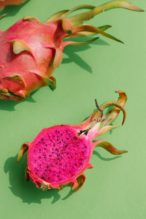 Overhead of bright pink slice of dragon fruit and part of whole fruit placed on green smooth surface