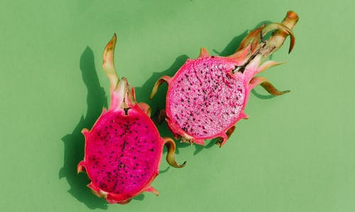 From above of fresh ripe dragon fruit cut in halves casting shadows placed on light green background