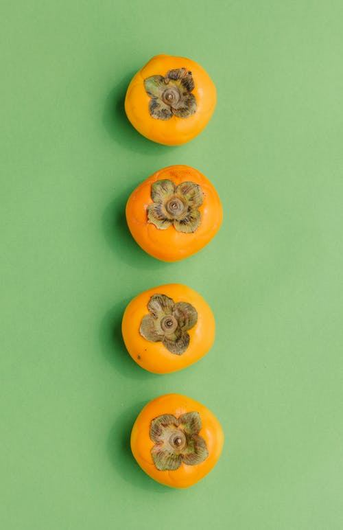 Persimmons in row on green background