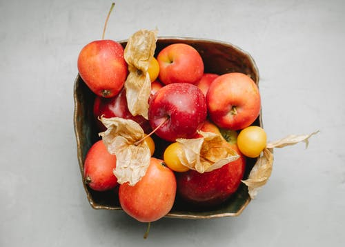 Top view of ripe red apples and yellow berries of physalis placed together in fruit bowl on gray background