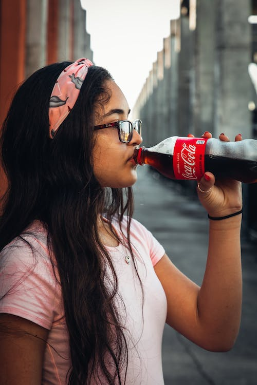 Woman in White Shirt Drinking Coca Cola