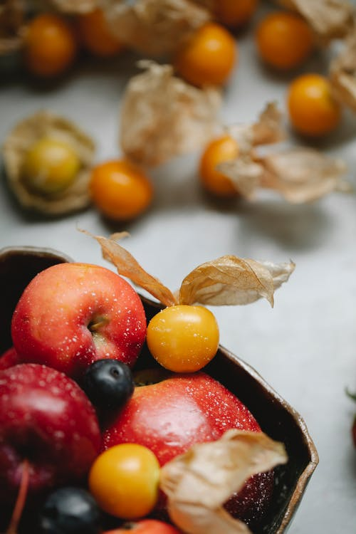 Delicious fruits in heaped in bowl and scattered on table