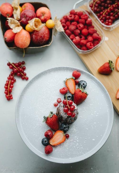 Клубника и черника на белой керамической тарелке