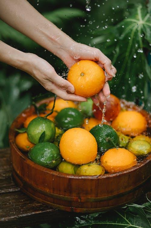 Persona Che Tiene La Frutta Arancione Sulla Ciotola Di Legno Marrone