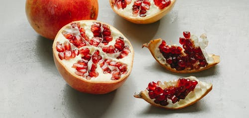 From above of fresh ripe red pomegranate placed on gray table in kitchen