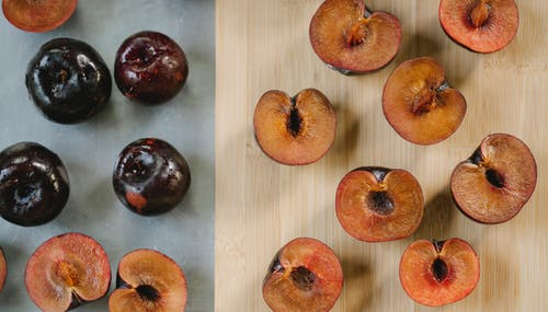 Ripe tasty plums on different backgrounds