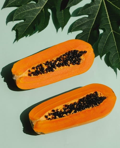 Top view of appetizing composition of ripe papaya with plant leaves on blue background