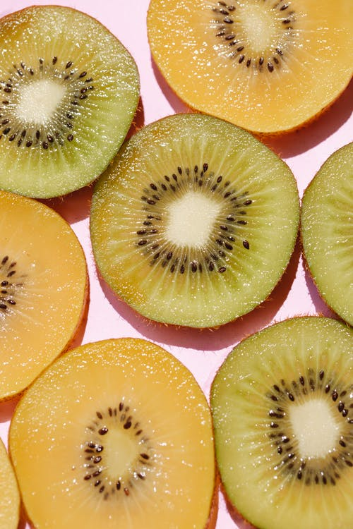 Top view of composed fresh tasty green kiwi slices placed on pink background