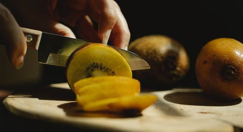 Closeup of crop unrecognizable female cutting fresh ripe kiwi with small sharp knife on wooden chopping board