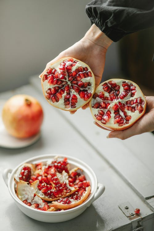 Crop woman with halves of pomegranate