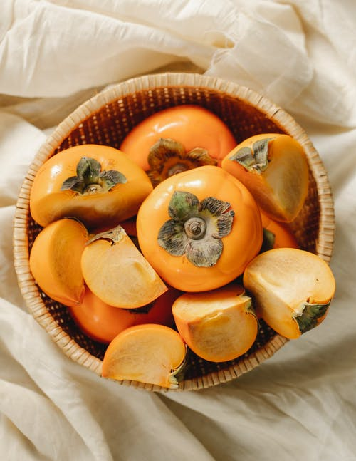 Whole and cut fruits of persimmons