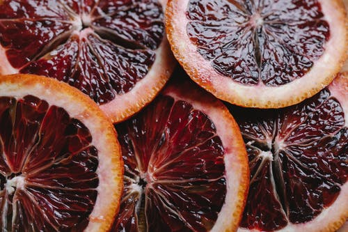 Top view closeup of sliced fresh ripe juicy tasty unpeeled fruit of red orange