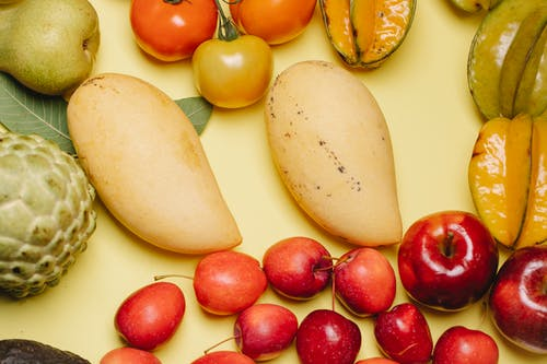 From above of assorted ripe fresh tasty healthy fruits placed on beige background
