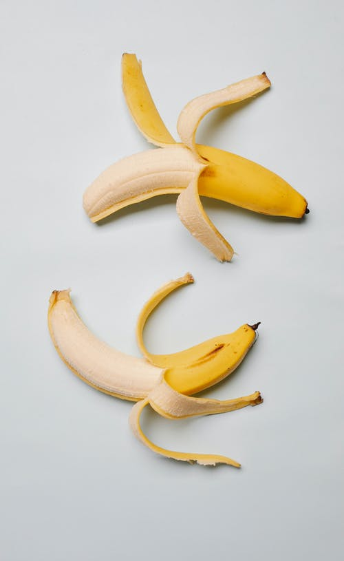 Top view of fresh ripe mellow yellow bananas with skin place on white background