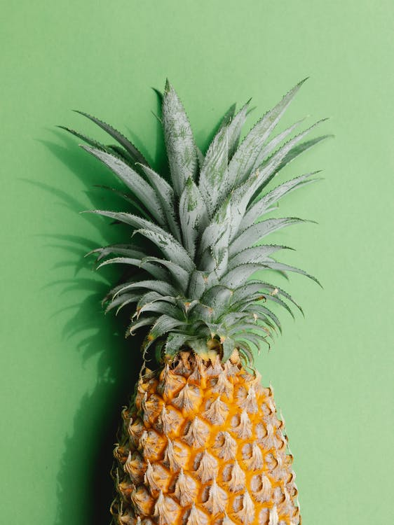 Top view exotic fresh ripe pineapple with bright leaves placed on green background