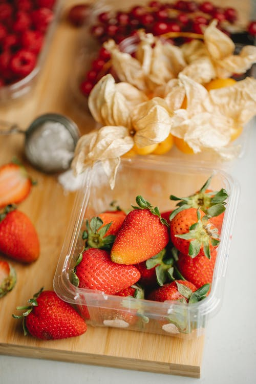 Fresh ripe strawberries in plastic container placed near ground cherry