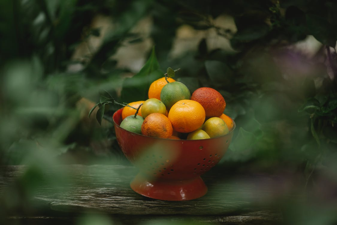 View through blurred foliage of fresh ripe oranges and mandarins with other exotic fruits placed in red colander on wooden shelf