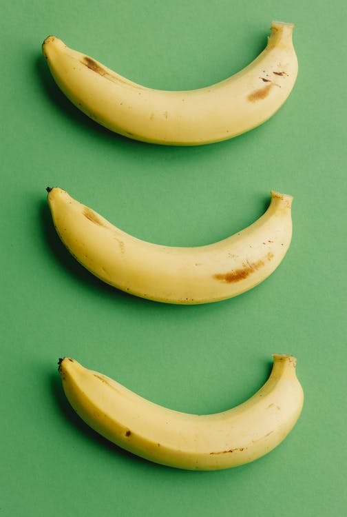 Top view composition of healthy ripe bananas with dark spots arranged in row on green background